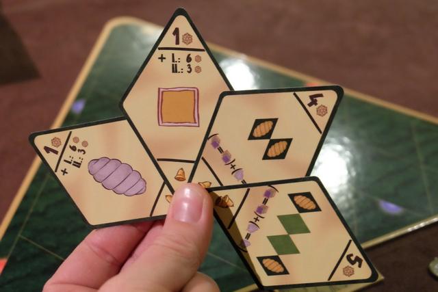 Chacun reçoit 4 cartes d'objectifs pour l'ensemble les 3 manches de la partie. En début de chaque manche, on en joue une qui s'appliquera à tous les joueurs, la dernière sera défaussée. En ce qui me concerne, donc, on voit que j'aurai intérêt à favoriser les décorations de type torsade (1PV / déco + 6PV ou 3PV pour le premier et le deuxième en majorité), les décorations jaunes (même calcul de PV), les paires de décorations identiques côte à côtes (même déco et même couleur), ou encore de démarrer et de terminer des lignes par les mêmes décorations. De base, je me dis que je vais garder les deux premières pour les manches 2 et 3, pour me laisser le temps de placer du jaune et des torsades...