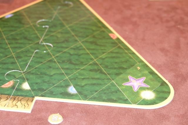 La mécanique centrale du jeu, ensuite, est basée sur du draft : on choisit une carte de sa main qu'on met face cachée devant soi, puis on passe les cartes restantes à son voisin de gauche. Ensuite, on retourne simultanément notre carte et on la place où on le souhaite sur notre sapin. Ci-dessus, vous voyez que j'ai mis une étoile violette, avec deux flocons de neige (donc 2PV en fin de partie) dans l'angle et que je complète ainsi la boule jaune.