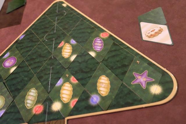 Chacun dispose de 3 cartes de gâteaux de Noël, utilisables une fois chacune pendant la partie, lesquelles étant des jokers permettant d'échanger deux cartes déjà placées sur le sapin. Ci-dessus, je m'apprête à en dépenser une pour améliorer la position de certaines de mes torsades comme vous allez le voir en comparant avec la photo suivante...