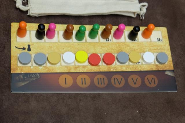 Les joueurs possèdent chacun deux pions d'actions, les orange pour Pierre, les noirs pour Antonin, les roses pour Jean-Luc, les marron pour Michel et les verts pour moi, ceux-ci étant placés dans l'ordre du tour, puis l'ordre inverse, pour déterminer qui agira. En-dessous, 11 disques aux couleurs des compagnies sont piochés depuis un sac et mis au hasard, chaque joueur en prenant un de son choix à son tour, soit pour le mettre sur le paysage (rail construit), soit pour le mettre sur son plateau individuel (titre acquis). Et cela formera aussi l'ordre du tour du prochain tour. Le dernier jeton, non pris, viendra recouvrir le n° du tour actuel en bas. Et cela désignera aussi les seules compagnies qui seront décomptées à la fin ! Pas placée ? Pas comptée !!! Hyper vicieux... ;-)