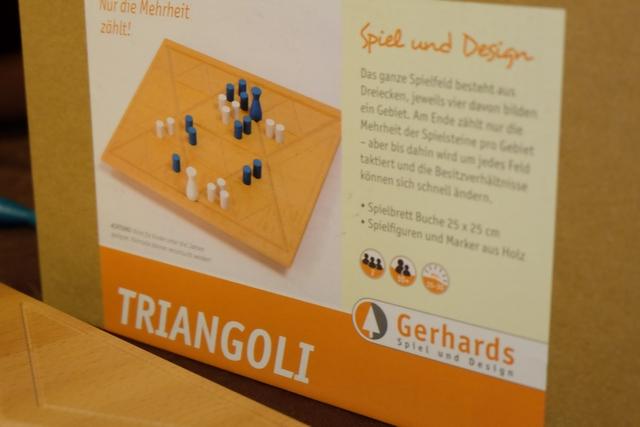 Triangoli est, de loin, le jeu Gerhards le plus attirant de par ses triangles gravés sur le plateau et ses pions aux couleurs claquantes. On a affaire, ici, à un autre jeu de majorité, avec une pose de pions qui dépendra, cette fois, du déplacement de la figurine de chaque joueur. Quelques similitudes avec Urbino, certes, mais ça s'arrêtera là...