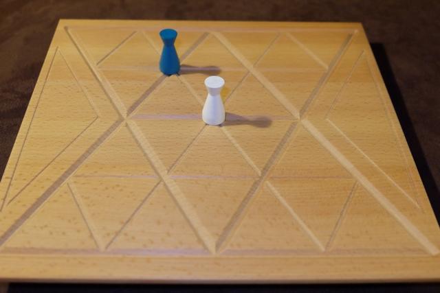 La mise en place consiste à positionner sa figurine sur l'intersection de son choix. Ensuite, chacun la déplacera à tour de rôle et posera autant de pions à sa couleur dans l'un des triangles vides adjacents à l'intersection d'arrivée que de segments parcourus, puis pourra faire un échange avec des pions adverses adjacents aussi. Un exemple ci-après...