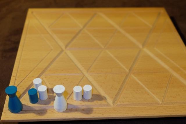 Ci-dessus, par exemple, Maitena a déplacé sa figurine bleue le long de la ligne sur une longueur de 3 segments et a placé 3 pions dans le triangle du coin. Mais, ensuite, j'ai fait glisser ma figurine blanche le long de la ligne d'à-côté sur une distance de 2 segments, ce qui m'a permis de placer 2 pions dans le triangle de droite, mais aussi d'échanger 2 pions bleus en blancs dans celui de gauche puisque ma figurine y est adjacente et qu'elle a été déplacée de 2 segments. Déconcertant...