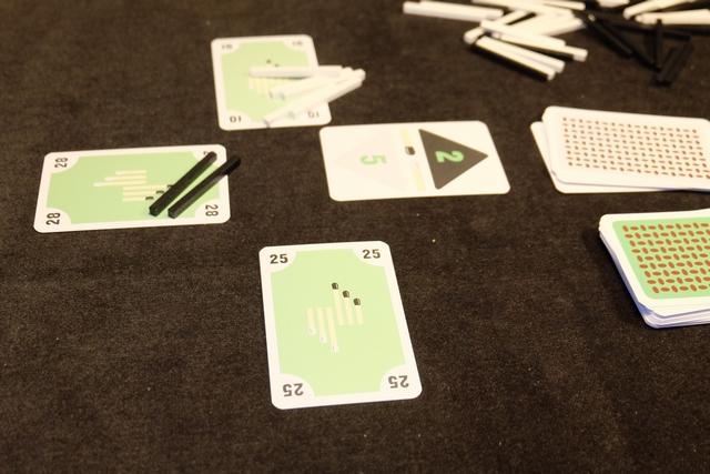 Petit rappel des règles : on dispose d'une main de 9 cartes avec des valeurs uniques de 1 à 50, on tire une carte avec une valeur sur fond noir (ici le 2) et une sur fond blanc (ici le 5), puis dans l'ordre du tour chacun joue une carte de sa main. Le joueur qui a joué la plus forte prend un nombre d'allumettes noires égal à la valeur inscrite (donc 2), le joueur ayant joué la carte la plus faible prend un nombre d'allumettes égal à la valeur inscrite (donc 5). Ci-dessus, Leila prend deux noirs et Maitena 5 blanches. Puis on recommence pendant 9 tours. Le but est d'équilibrer ses prises de noires et de blanches pour s'approcher d'un score de 0.