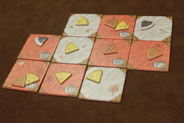 A trois joueurs, le plateau de tables à constituer est celui ci-dessus : la seule différence entre les rouges et les blanches est que les blanches ont une valeur de dé indiquée afin d'ajouter, en tout, deux parts de victuailles, en plus de celle présente sur chaque table, au début de la manche. Il y a trois types de victuailles : le fromage avec 30 exemplaires, la pizza avec 20 exemplaires et la tarte aux fruits avec 10 exemplaires.