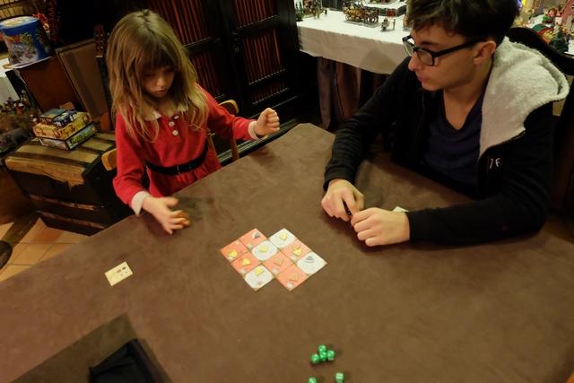 Nous jouons à 3 joueurs : Leila avec les dés orange, Tristan avec les dés noirs et moi-même avec les dés verts. A son tour, on lance tous les qui nous restent et on doit affecter tous ceux d'une même valeur à la table de son choix (au départ) ou sur une où on est déjà présent (avec la même valeur) ou adjacente (avec une valeur qu'on n'a pas encore posée). Comprendo ?