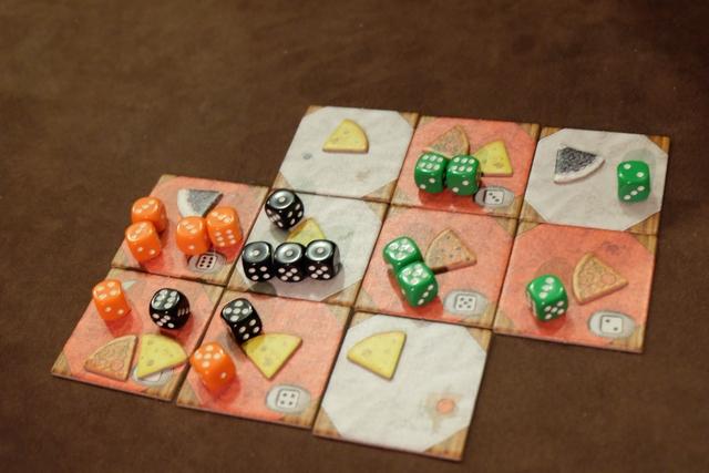 Voici comment se termine cette première manche : Leila empoche une part de tarte avec ses quatre dés de valeur 3, Tristan empoche une part de pizza et deux parts de fromage avec ses dés de valeurs 6 et 1, tandis que, de mon côté, j'empoche toutes les parts de droite avec uniquement mes dés verts. Se répartir, en se réservant des zones, semble être une -très- bonne chose... ;-)