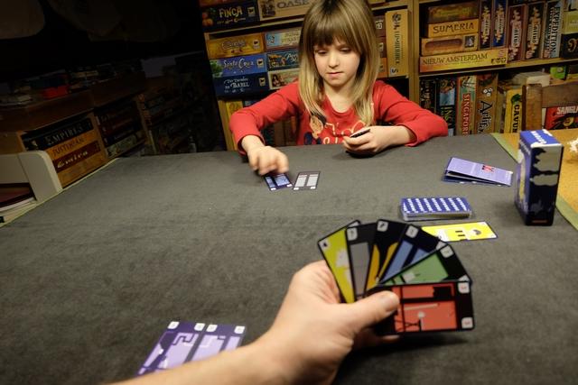 A son tour, le joueur actif pioche une carte (sauf s'il en a déjà 8) puis joue, s'il le souhaite, autant de cartes que voulu. Le plus souvent, on joue deux cartes pour se créer un étage, mais on peut aussi être beaucoup plus méchant avec les autres joueurs, en les attaquant au moyen des cartes spéciales jaunes et orangées (j'en ai deux dans ma main). A noter que certaines cartes sont des jokers (les grises).