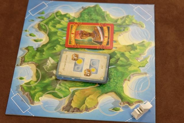 Le -tout- petit plateau commun représente l'île qui renferme les précieux trésors, objet de notre quête. Elle est divisée en quatre côtes (les quatre côtés du plateau), chacune divisée en deux territoires (les deux cercles). Un bateau sillonne les côtés dans le sens inverse des aiguilles d'une montre et on explorera, à chacune des cinq manches de la partie, la côte pointée par la proue du bateau. Explorer veut dire qu'on vérifiera qu'il y a suffisamment de cartes en face des deux territoires concernés afin d'en récupérer les trésors...