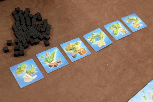 Chaque joueur, à son tour, a le choix entre passer, poser des cartes face à un territoire (on revient sous peu sur les contraintes de pose) et activer l'une des tuiles de petites îles visibles ci-dessus, contre la défausse de deux cartes de même couleur. Ensuite, la tuile est retournée pour la suite de la manche et donc inutilisable. Les tuiles permettent de faire avancer le bateau d'un cran (très vicieux tout ça !), de défausser 3 cubes de malédiction, ...