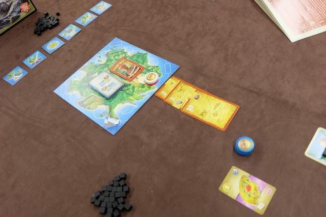 Voici la situation en fin de premier tour de jeu, avec la pose d'un disque rouge et de la carte marron 2 pour Jean-Luc en face d'un territoire, l'activation d'une tuile de petite île (prise d'un cube de malédiction et d'une carte de trésor, le bijou violet ci-dessus) pour Fabrice, et ajout des cartes 3 et 10 marron, pour moi, ainsi que la pose d'un de mes disques blancs sur le même territoire que Jean-Luc. Et oui, dans ce jeu, il faut savoir coopérer un minimum pour arriver à ce qu'il y ait assez de cartes sur un territoire pour être exploré (à trois joueurs, il en faut 4 au minimum).