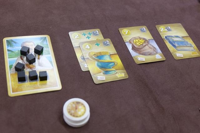 Voici mon butin en fin de première manche, avec deux cartes de couronne (rapportant les PV indiqués en jaune + des PV en fonction de la majorité sur les croix vertes), une carte de sac d'or et une carte de livre (rapportant en PV 2 fois la valeur d'une malédiction récupérée sur une autre carte).