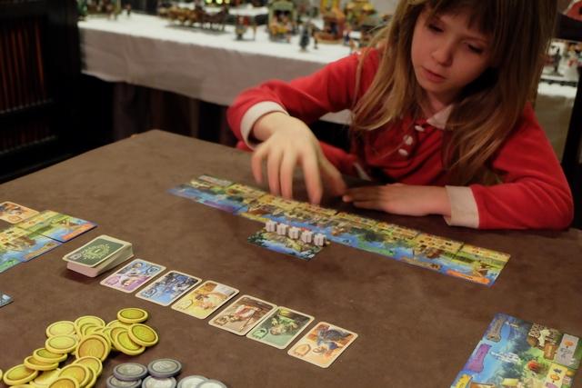 Oui, vous voyez bien, Leila fait partie des 3 joueurs attablés (Tristan, elle et moi) ! En effet, même si le jeu semble basé sur de la combo de cartes à fond, sur de la gestion de ressources (les meeples), sur un calcul de PV à la fin à base de diversité et de majorités, oui, Leila peut y jouer, le jeu étant prévu pour 7 ans minimum. Et elle a 7 ans et 2 mois. Donc, allez, on y va...