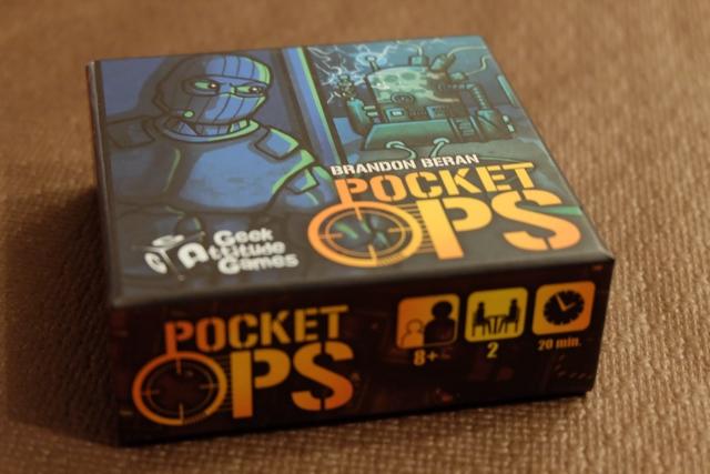 Toute petite boîte, d'à peine 8 cm de côté, ce Pocket Ops est la nouveauté d'Essen des amis de GAG, un jeu qu'ils localisent en France pour notre plus grand plaisir. Totalement en dehors de leurs jeux habituels, ce jeu est uniquement pour deux joueurs et franchement abstrait. Je vous dis en plus un peu plus bas...