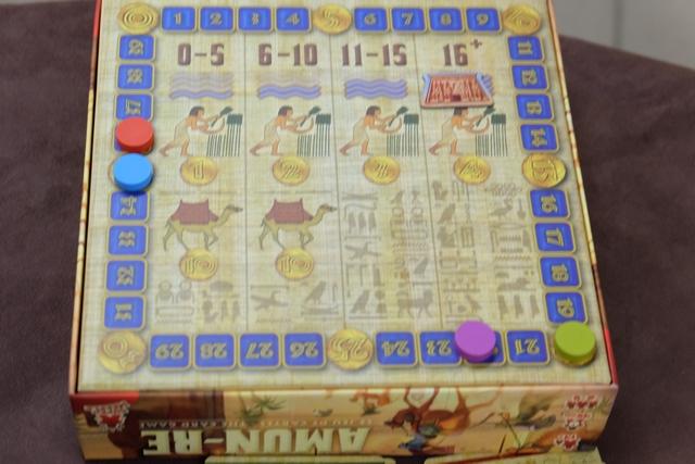 Après trois tours d'enchères, on passe à l'offrande à Amun-Re. Chaque joueur, parmi les cartes qui lui restent, choisit face cachée celles qu'il offre à Amun-Re, puis elles sont toutes révélées simultanément. Le total est fait et on déplace le marqueur de temple sur la colonne correspondante (sur le dessous de la boîte). Le joueur ayant donné le plus récupère 3 pyramides qu'il place de manière équilibrée sur ses cartes de royaumes. Le deuxième en prend 2 et fait de même. Tous ceux qui ont misé au moins 1 sou en prenne 1. Enfin, chacun fait avancer son marqueur de revenu en fonction de la valeur des champs (ici 4 par champ) et du nombre qu'il en possède. Par exemple, le joueur rouge, c'est-à-dire Pierre, dispose de 36 sous pour construire et prévoir sa main de cartes pour l'âge 2.