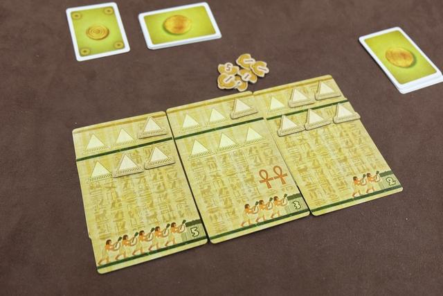 Petite vue de mon royaume en fin d'âge 2, avec 6 pyramides sur chaque série de cartes et plus de 9 champs en tout, d'où un petit bonus de 1PV bien apprécié. Par contre, qu'est-ce que j'ai mal joué lors de l'offrande à Amun-Re ! En effet, j'ai gardé deux cartes, la 1 et la 3, ne misant que la 2, ce qui m'a pénalisé à plusieurs titres : je n'ai obtenu qu'une pyramide de récompense au lieu de 2, voire 3, et, surtout, cela n'a pas emmené le marqueur de temple sur la 4ème colonne, ce qui n'a rapporté que 3 sous par champ au lieu de 4 (j'ai donc perdu la bagatelle de 10 sous avec mes 10 champs !!!).