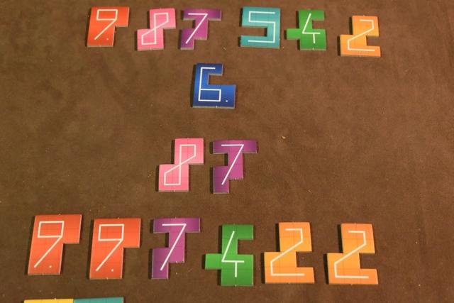 Et, pour vous montrer les points faits par chacun, on a étalé les tuiles concernées : Leila marque 6 points fois 2 avec son 6, puis (9+8+7+5+4+2) fois 1 avec les autres ; tandis que moi je marque (8+7) fois 2 et (9+9+7+4+2+2) fois 1.