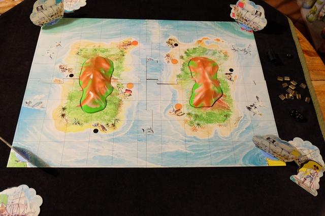 Le plateau est assemblé, sur la table, même s'il vaut mieux jouer par terre à ce jeu. En effet, les boulets de canon ont tendance à voler en tous sens, je m'en souviens, mais on sera quand même (surtout moi !) plus à l'aise assis sur une chaise... Rappel du but du jeu, à deux joueurs : à partir de deux navires qu'on possède, aller ramasser 3 trésors sur les îles centrales et les rapporter dans nos repaires.