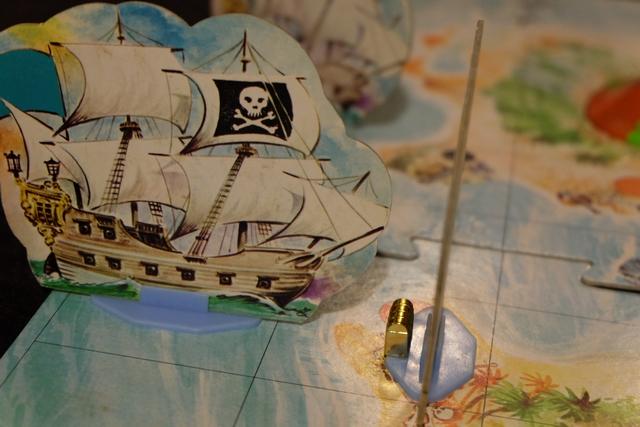 Ah ah, je viens de charger mon premier trésor, au nez et à la barbe du bateau bleu de Leila. A noter que le positionnement du bateau par rapport aux points noirs du plateau n'est pas neutre : en effet, c'est à partir de ces points que l'on peut, éventuellement, utiliser un canon pour tirer un boulet sur un bateau adverse, donc autant placer ses bateaux sur la tranche plutôt que de face....