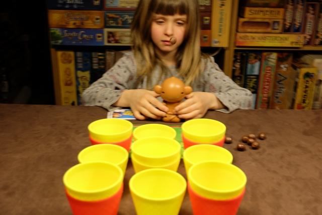 Un carré de 3 par 3 constitué avec des gobelets jaunes et rouges. Objectif : réussir à projeter des noix de coco dans 6 d'entre eux pour constituer une pyramide devant soi avant son adversaire. A noter la présence de la noix de coco que Leila vient de projeter, entre sa bouche et son nez ;-)