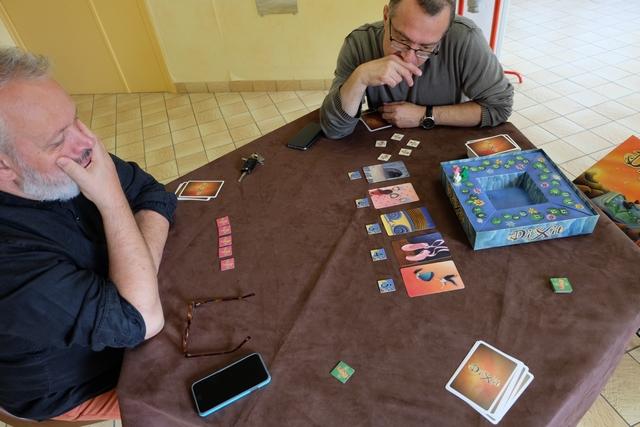 """Nous jouons à 3 joueurs, avec Christian, Fabrice et moi-même. Comme je suis le premier conteur, je place une carte sur la table, face cachée évidemment, contre 2 pour chacun des autres joueurs, d'où un total de 5 cartes, quand même, une fois étalées face visible. Pour mon premier tour, je propose : """"De deux maux, il faut choisir le moindre""""."""