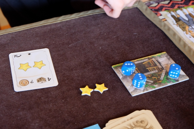 Maitena voit une fenêtre dans l'acquisition simplissime et immédiate de pas moins de 2 étoiles (il en faut 6 pour gagner). Elle acquiert donc cette carte pour 4 dés de même valeur et la valeur d'un dé en boutons.