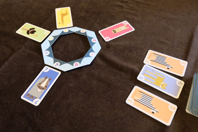 Ce jeu simule la chaîne alimentaire (absolument non réaliste par contre), avec un plan d'eau central hexagonal, autour duquel vont venir se placer les animaux en face du n° qui leur est attribué (le rhino, par exemple, se met toujours en face du 7). Lorsque trois animaux identiques, ou plus, sont placés, le joueur qui vient de procéder à ce placement (depuis sa main de 5 cartes) récupère la première série d'animaux de valeur inférieure. Ce seront ses PV. Et c'est tout ! Ou presque... Je vous parle de la souris et de l'éléphant dans peu de temps.