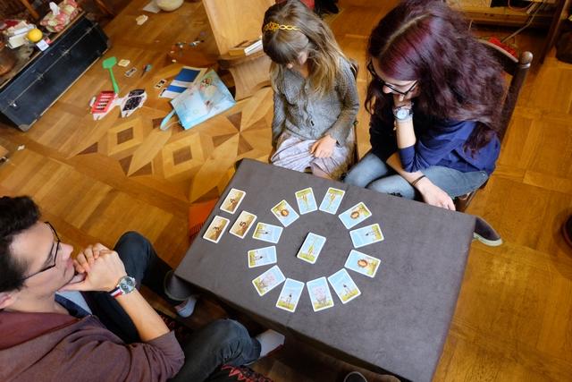 Nous jouons à 4, avec Joris, Leila, Maitena et moi-même. L'installation consiste en la pose de 12 cartes sous forme de cercle, correspondant aux animaux visibles pour notre safari photos. L'idée est d'en avoir 3 de suite, dans le même ordre que la carte 3 que nous avons chacun en main, pour pouvoir la valider. Ensuite, on en refera 3 autres chacun de valeur 3, puis 3 de valeur 4 (avec 4 animaux) et 2 de valeur 5 (avec 5 animaux). A son tour, on peut modifier différentes choses de la position centrale, évidemment...