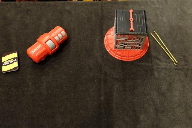 Le matériel est constitué d'une cage où est enfermée une première clé, à droite, d'une sorte de gros cylindre où est enfermée une deuxième clé, au centre, lequel s'ouvrira si on résout correctement 3 énigmes successives provenant du set de cartes à gauche. Allez, c'est parti !