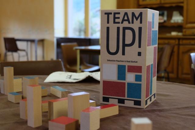 La boîte de Team Up ! et son matériel : absolument somptueux ! Le jeu simule un empilement de cartons sur une palette, de manière coopérative, sachant qu'à son tour on pioche une carte qui indique soit la couleur soit la forme du carton à placer.