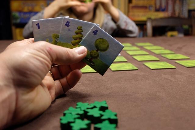 """Mes 3 tuiles de départ proviennent de 3 séries différentes (dino de valeur 1, """"sapin"""" de valeur 4 et """"deux boules"""" de valeur 4). Devant moi, j'ai aussi 8 pions verts que je vais tenter de placer le mieux possible autour des tuiles étalées, afin qu'ils voient, en ligne, colonne ou diagonale, un maximum de topiaires (arbres sculptés) de valeur croissante, de la même série si possible."""