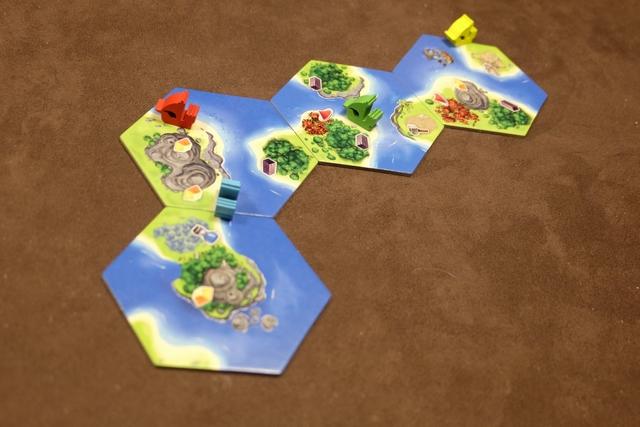 Voici donc notre configuration de départ, avec les 4 premières tuiles posées et les bateaux de chaque joueur. La vraie partie peut démarrer. A son tour, le joueur actif utilise des cartes de sa main (6 différentes) en payant leur coût avec ses cartes (un peu comme dans San Juan). Puis, il produit avec ses pionniers placés sur des zones de production (ébène, épices, teinture, or) et, enfin, il pioche autant de cartes que 3 + nombre de bateaux à sa couleur + nombre de forts construits.