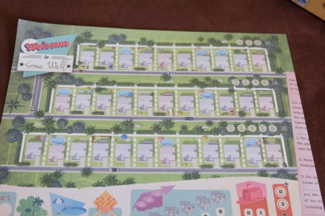 Chaque joueur dispose d'une feuille de bloc (grande taille et en couleurs !) pour noter au fur et à mesure de la partie ce qu'il a construit dans sa ville. Ci-dessus, vous pouvez voir mes trois rues de longueur différente (10, 11 et 12 maisons potentielles), avec une barrière à chaque extrémité et quelques emplacements de piscines dans certaines. Petit à petit, chacun va noter sur sa feuille un numéro de maison dans l'une de ses rues, en fonction des 3 cartes de numéros tirées au hasard à chaque tour. Puis, il fera une action complémentaires qui avait été affectée, aléatoirement, à ce numéro. La seule vraie règle, c'est que les numéros dans les rues doivent toujours être en ordre croissant.