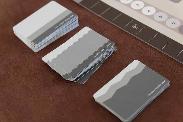 Le jeu nous entraîne à la préhistoire, au travers des trois époques qui l'ont jalonnée : le Trias, le Jurassique et le Crétacé. Ce qui est vraiment sympa, c'est que chaque pile de cartes comporte uniquement des fossiles de l'époque concernée, avec une jolie couche plus ou moins épaisse pour se repérer au dos des cartes, toujours dans les mêmes tons de gris.