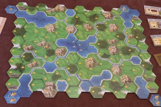 Le plateau principal est composé de 4 parties modulaires, assemblées dans un ordre immuable (A B C D) mais avec le choix de deux faces à chaque fois (1 ou 2). On imagine que ça doit en donner des possibilités... Les hexagones indiquent le type de terrain (loch pour les cases bleues, prairie, forêt ou montagne) mais avec des finesses rarement vues ailleurs : sur une même case, on peut avoir un peu de plusieurs de ces types de terrain. Du coup, en fonction de l'élément qu'on veut placer, on aura le droit de le faire, pourvu qu'il y ait au moins un peu du type visé. Cela rend le jeu graphiquement plus réussi car on n'a pas de frontières trop nettes d'un hexagone à l'autre. A noter la présence de rivières qui coulent, parfois, entre les hexagones pour relier les lochs.