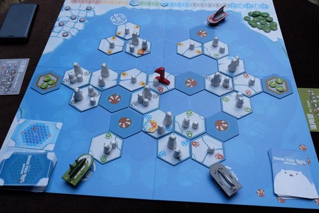 Le jeu vient d'être mis en place, avec un positionnement aléatoire des tuiles de banquise et des ours arrivant en proportion de la couleur du n° de leur tuile. Nous jouons à ce jeu coopératif à 3 joueurs, Fabrice avec le bateau gris (White Wave), Julie avec le vert (Icy Cape) et moi-même avec le rouge (Breeze Dragon).