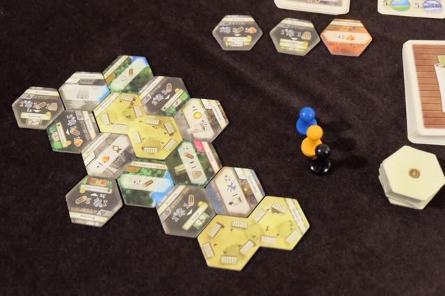 Nous venons de placer les différentes tuiles marquées d'un 0 au dos (avec celle du Diplomate mais sans le Key Laborer) et les deux marchés. C'est Florent qui a commencé et c'est lui qui va entamer la partie avec son Steward noir, Béatrice jouant le bleu et moi-même l'orange.