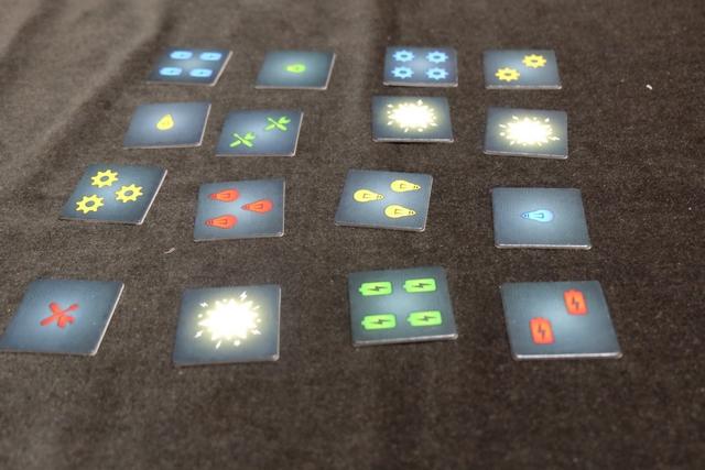 Voici les 16 tuiles de notre première manche sur les 3 que comptera la partie. Chaque tuile comporte 3 informations : le nombre (de 1 à 4), le type d'objet (ampoule, engrenage, pile ou outils) et la couleur (bleu, vert, jaune ou rouge). Trois tuiles sont des explosions sur lesquelles je reviendrai. Au bout d'une minute d'intense mémorisation (chacun utilise la technique de son choix), les 16 tuiles sont retournées et la première manche débute vraiment.
