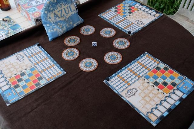 Le jeu est tout bonnement magnifique ! Au centre de la table, pour notre partie de découverte à 3 joueurs, les 7 fabriques de pierres, autour les plateaux individuels de chaque joueur et, au-dessus, le splendide sac bleu renfermant les pierres que l'on va piocher par la suite...