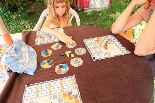 En cours du premier tour de la première manche, après que Julie et moi avons choisi nos tuiles, Leila fait de même. Sur le plateau de Julie, on peut voir qu'elle a choisi 2 tuiles rouges qu'elle a positionnées pour compléter directement sa ligne de taille 2. Puis, elle a mis au centre de la table les 2 autres tuiles colorées qui étaient dans la fabrique.
