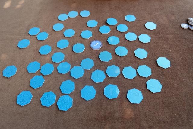 Au début de chaque manche (une partie en compte trois), tous les jetons heptagonaux sont étalés face cachée sur la table, sauf un au centre. Chaque jeton renferme une valeur de 1 à 15 et il y en a trois de chaque, sauf la valeur 7 qui en compte sept. A son tour, le joueur actif commence par retourner un jeton qui est sur la table, puis il a le choix entre prendre un jeton visible ou caché, ou rendre un jeton qu'il avait déjà pris, visible ou caché. Les jetons visibles restent visibles, les jetons cachés restent cachés.