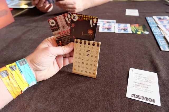 """En fait, David a même posé deux cartes face cachée car, au premier tour, c'est ce qui lui est demandé de faire, probablement pour bien brouiller les pistes (voir en arrière-plan). De mon côté, j'ai pioché deux cartes dans les piles de mon choix, la 10 et la 16, puis je les ai barrées sur mon bloc de saisie d'informations, car le fugitif ne peut pas s'y rendre, je les ai ! Mon but est de parvenir à identifier toutes ses planques successives, les cartes de sprint (pas) se révélant immédiatement si j'identifie la carte numérotée. Donc, à chaque tour, je peux dire """"Je pense que tu es passé par le lieu n°4"""" par exemple. Si c'est vrai, il retourne la carte, sinon il ne dit rien et à moi de trouver comment noter efficacement cette information à l'instant t sur mon bloc. Mais je peux prendre encore plus de risques en annonçant plusieurs lieux en même temps. Je dois les trouver tous en même temps sinon le fugitif ne dit rien. Risqué..."""