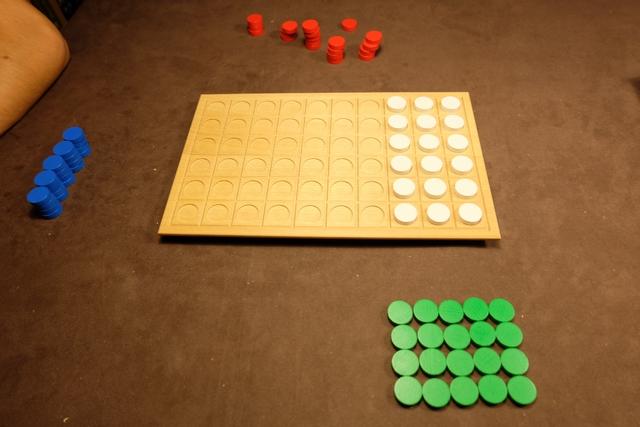 A trois joueurs, une zone du plateau est inutilisée. Chacun prend 20 pions circulaires à sa couleur, les bleus pour Joris, les rouges pour Maitena et les verts pour moi. Le but sera d'aligner 4 pions soit horizontalement, soit verticalement, soit en diagonale, et même en profitant de la 3 D !