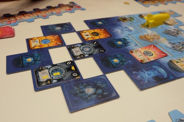 Petit exemple d'expulsion de la dernière bande, lorsqu'un joueur (moi en l'occurrence) a joué une carte 0 quelque part sur le plateau (sur la dernière bande en l'occurrence aussi). Avant de la retirer, l'astronef est avancé d'une case vers l'avant. Puis les joueurs qui ont des cartes sur celle-ci Docky et moi donc) vont récupérer quelques ressources ou bonus : Docky prend 1PV car il avait bien placé sa carte sur une case produisant de l'eau et, de mon côté, je prends une pierre + un blé car c'est ce qui est indiqué en bas de la carte (zone grise). Ensuite, la bande est retournée côté jour est va être placée tout devant.