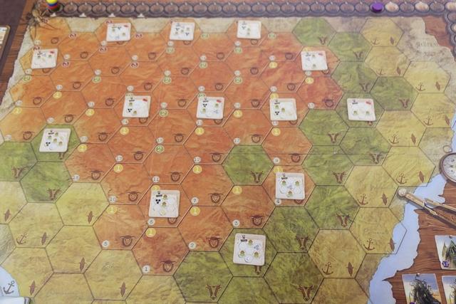 En début de partie, le plateau est étalé, majestueux, avec des tuiles de mise en place positionnées sur certaines cases identifiées. Celles-ci indiquent ce qui doit être placé sur elles, ou sur leurs voisines, avec des éléments positifs (comme des ressources par exemple) ou beaucoup moins (comme des Grands Anciens...). Vous remarquerez déjà les trois couleurs de terrains : la côte en jaune, la prairie en vert et l'outback en marron.