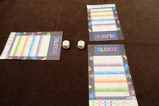 """Chaque joueur dispose d'une feuille de papier avec différents niveaux de couleur et 7 cases par étage. A son tour, le joueur actif, ici Maitena placée à ma gauche, lance les deux dés et choisit l'une des deux formes obtenues puis la place tout en bas de son """"plateau"""" en faisant des croix sur les cases où il y en a et en traçant un cercle sur la case indiquée sur la face du dé, laissant apparaître, éventuellement, une valeur de PV. Le joueur suivant, Tristan en l'occurrence, prend le dé de son choix mais, s'il prend le même que Maitena, il ne tracera pas de cercle mais une croix sur la case en question. Et je fais de même, seulement pénalisé si je prends le même que Maitena. Forcément, on a intérêt à prendre l'autre..."""