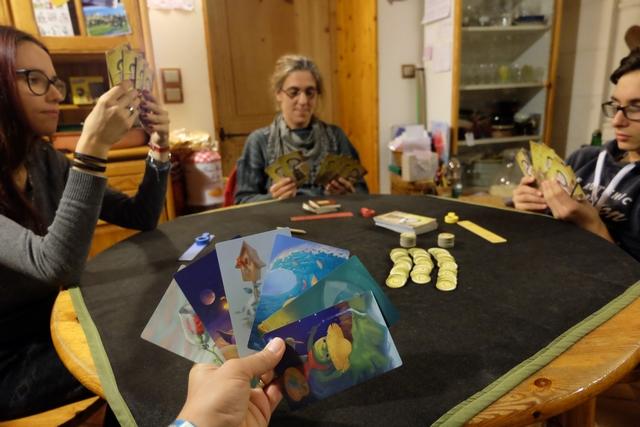 Il y aura 8 manches, soit deux fois le nombre de joueurs, puisque nous nous la faisons entre famille de grands : Maitena, Julie, Tristan et moi. On sent déjà, clairement, le bon moment prévisible... ;-) Ci-dessus, vous pouvez voir que chacun a 6 cartes en main, avec des illustrations, à la Dixit, de toute beauté. Le joueur actif, Julie pour la première manche, va placer une carte devant elle en rapport avec un mot auquel elle pense. Puis, elle écrira ce mot sur deux carnets sur les trois, les mélangera, avant de les distribuer aléatoirement entre Tristan, Maitena et moi-même. Chacun de nous va, ensuite, devoir jouer une carte devant lui, en rapport avec le mot lu. Même le joueur qui n'a rien d'écrit sur son carnet...