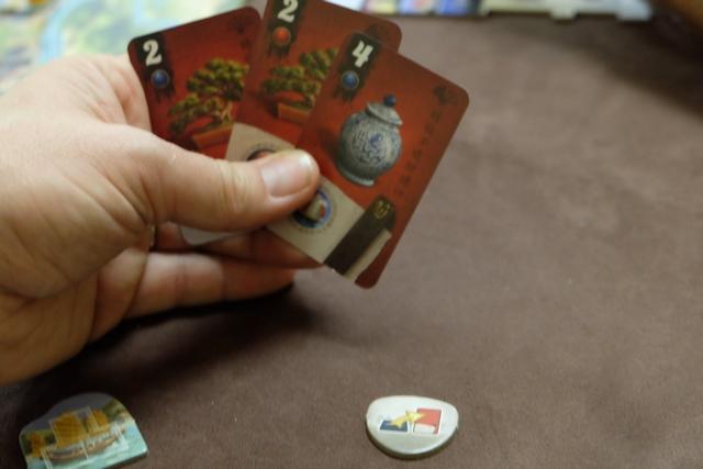 En faisant un voyage, dans la zone du même nom, je récupère la tuile ci-dessus, laquelle me permet de reprendre en main l'une de mes cartes défaussées (en fait cadeau récupéré sur un lieu). Du coup, je vais jouer un tour de plus que mes partenaires, car il m'en reste encore trois !