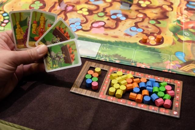 Chaque joueur dispose d'une main de 4 cartes, piochées au hasard. Ci-dessus, pour démarrer la partie, j'ai une carte violette, une rouge et deux grises, pour déplacer donc les fourmis correspondantes, en essayant de livrer, donc, les cylindres roses, orange et verts ! A droite, vous pouvez voir l'étendue de tout ce que je vais devoir livrer pour atteindre la fin de la partie... Mais, je n'ai accès qu'aux 7 cylindres que j'ai choisi de placer dans le petit compartiment de gauche.