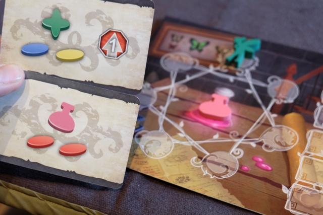 En début de partie, chaque joueur dispose de 2 cartes de départ, à partir desquelles il en choisira une pour démarrer sa partie. J'hésite encore avec les miennes : celle du haut pour empocher directement une graine verte, une autre bleu et une dernière jaune, plus 1 progression dans la piste rouge, et celle du bas, avec 2 graines rouges et 1 potion magique sur laquelle je reviendrai. Que feriez-vous ?